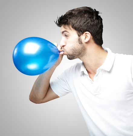 portrait of young man blowing a balloon over grey background photo