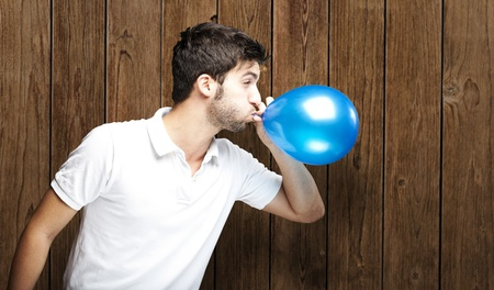 inflating: portrait of young man blowing balloon against a wooden wall