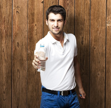 portrait of young man holding water bottle against a wooden wall photo