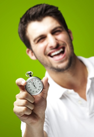 portrait of young man holding a stopwatch against a green background photo