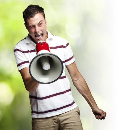 portrait of young man shouting with megaphone against a nature background photo