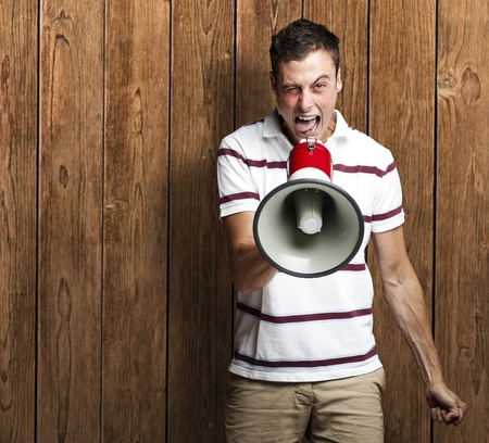 portrait of young man shouting with megaphone against a wooden wall Stock Photo - 11507973