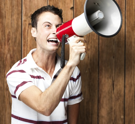 portrait of young man shouting with megaphone against a wooden wall Stock Photo - 11507827