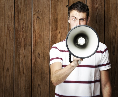 portrait of young man shouting with megaphone against a wooden wall Stock Photo - 11507894