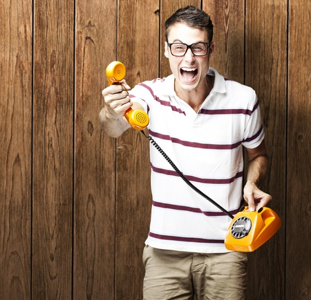 joking: portrait of young man holding a vintage telephone against a wooden wall