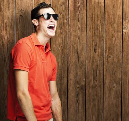 portrait of young man shouting and joking against a wooden wall Stock Photo - 11507971