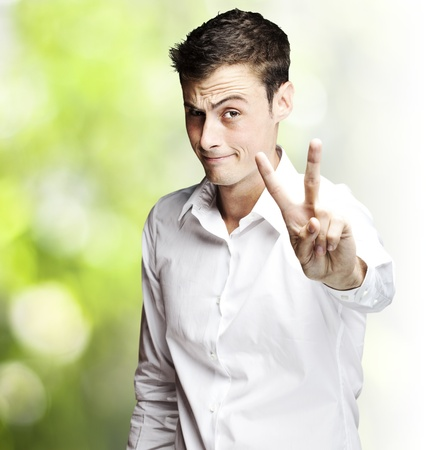 hand gestures: portrait of young man doing peace symbol against nature background