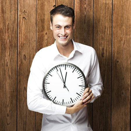 portrait of young man holding clock against a wooden wall photo