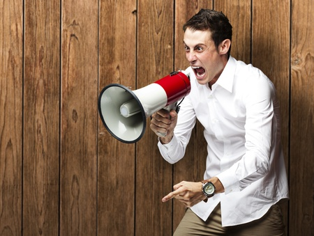 crazy man: portrait of young man shouting with megaphone against a wooden wall