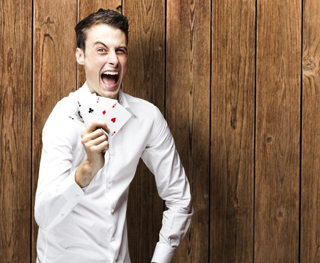 portrait of young man shouting with megaphone against a wooden wall man holding poker cards against a wooden wall photo