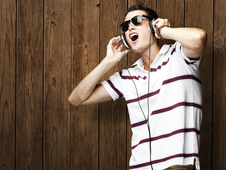 portrait of young man listening to music against a wooden wall Stock Photo - 11507951