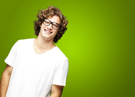 intellectual: portrait of a handsome young man smiling against a green background