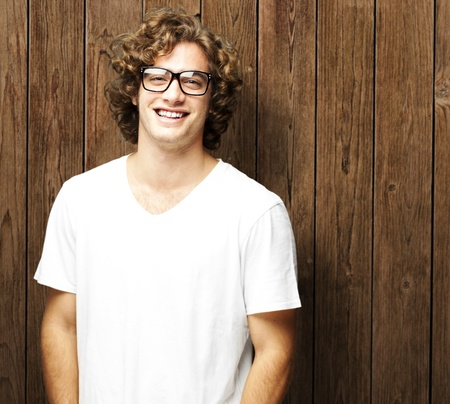 glasses model: portrait of young man smiling against a wooden wall