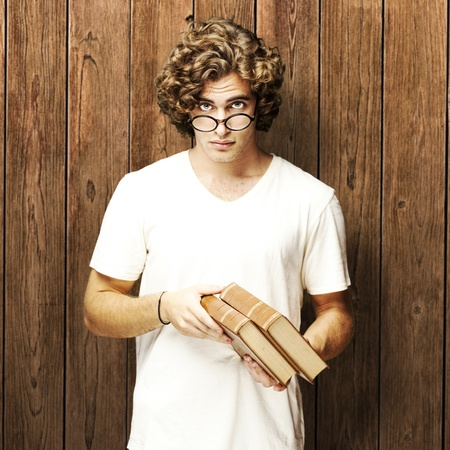 portrait of young student holding books against a wooden wall photo