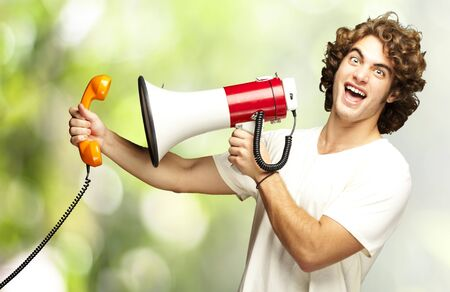 portrait of young man shouting with megaphone and talking on vintage telephone against a nature background photo