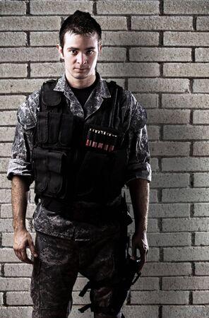 iraq war: young soldier against a grunge bricks wall