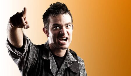 portrait of young soldier shouting and pointing with the hand against a orange background Stock Photo - 12105400