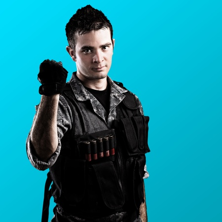 young soldier clenching the fist on a blue background photo