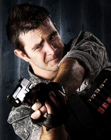 man holding gun: portrait of young soldier aiming with gun against a grunge wall