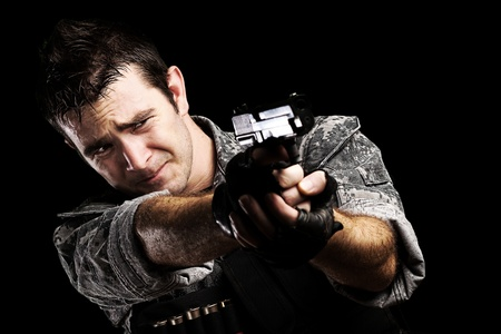 portrait of young soldier pointing with a gun against a black background photo