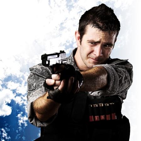 pistola: retrato de un soldado asustado con el objetivo con el arma contra un fondo de cielo nublado Foto de archivo