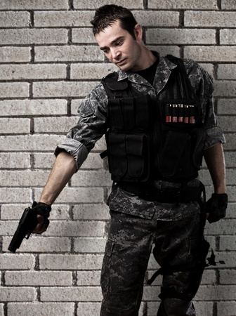 kill: young soldier pointing to the ground against a bricks wall