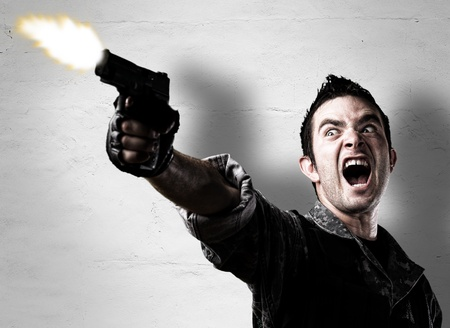 hombre disparando: hombre disparando un arma de fuego contra una pared erosionada