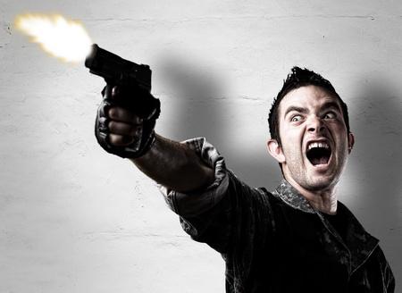 vintage gun: man shooting a gun against a eroded wall