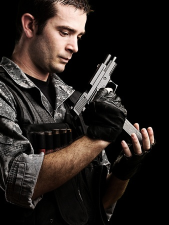 portrait of young soldier reloaing his gun against a black background photo