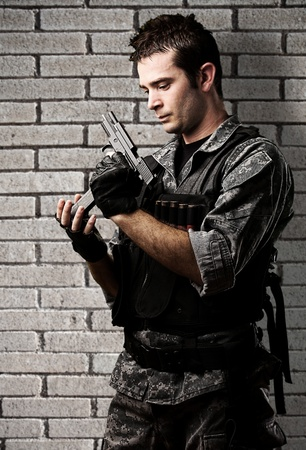 reloading: portrait of young soldier reloading the gun against a grunge bricks wall Stock Photo