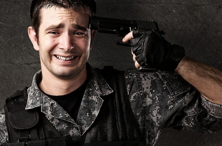 armed forces: portrait of young soldier committing suicide against a grunge wall