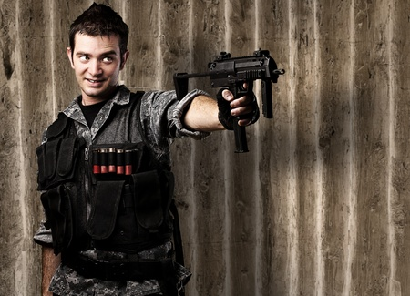 portrait of young soldier aiming with rifle against a grunge wooden wall Stock Photo - 12104812