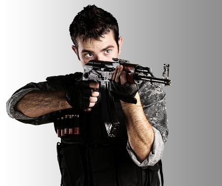 sniper: portrait of young soldier pointing with rifle against a grey background Stock Photo
