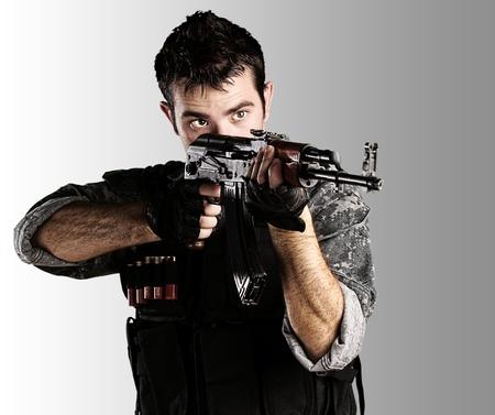 snajper: Portret młodego żołnierza, wskazując z karabinem na szarym tle Zdjęcie Seryjne