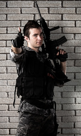 man holding gun: young soldier with rifle with finger up against a grunge background