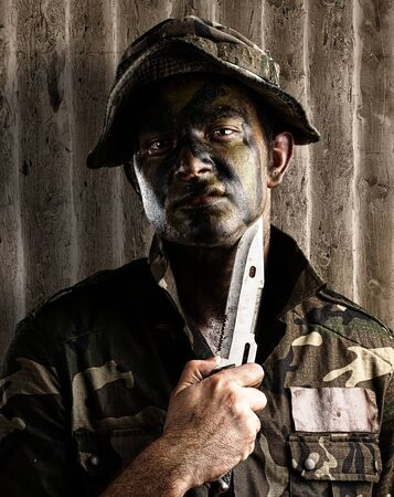 portrait of young soldier threating to suicide against a grunge wall Stock Photo - 12104459