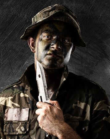 young knife: portrait of young soldier threating to suicide against a metal wall