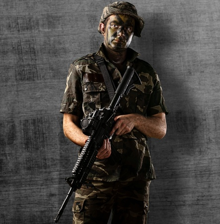 old rifle: portrait of young soldier holding rifle against a metal wall