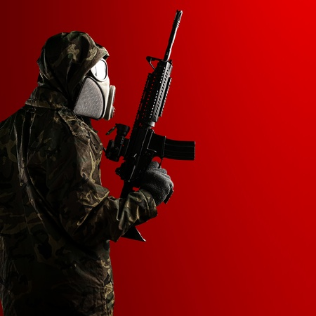 portrait of young soldier with rifle and gas mask against a red background photo