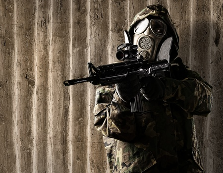 portrait of soldier with gas mask aiming with rifle against a wooden wall photo