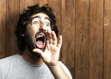 loco: retrato de hombre joven gritando contra una pared de madera Foto de archivo