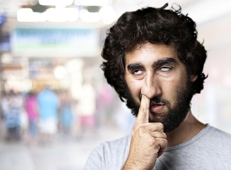 nosa: Młody mężczyzna z palcem w nosie na zatłoczonym miejscu
