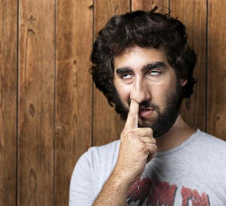 manos sucias: Retrato de hombre joven con el dedo en la nariz contra una pared de madera