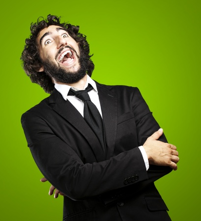 portrait of young man laughing against a green background photo