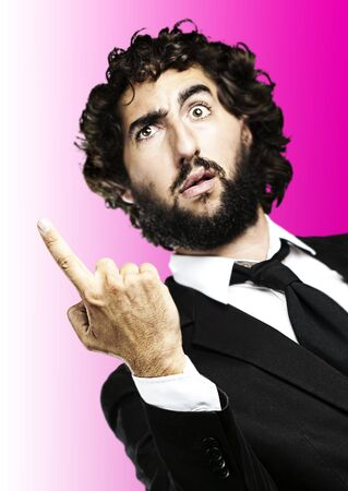 portrait of business man pointing up over pink background photo