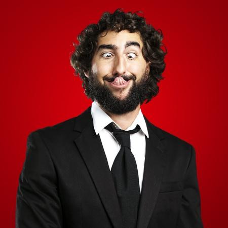 Porträt der jungen Geschäftsmann, der die Zunge zeigt auf rotem Hintergrund Standard-Bild