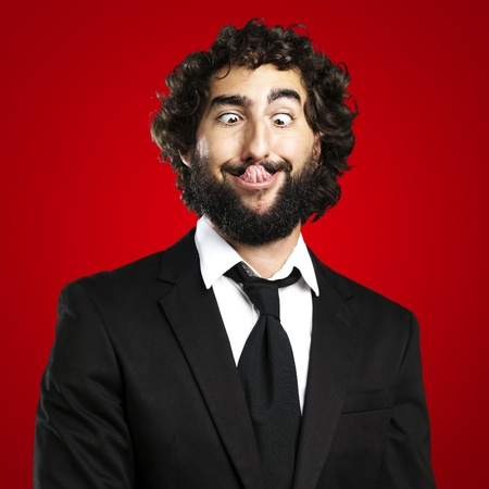 portrait of young business man showing the tongue over red background photo