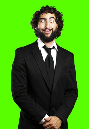 ugly mouth: portrait of young business man showing the tongue against a removable chroma key background Stock Photo