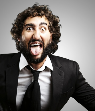 portrait of young man joking and showing the tongue over grey background photo