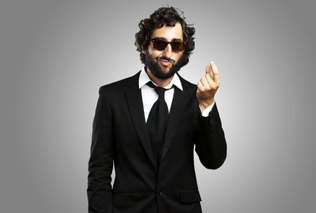 portrait of young business man gesturing money over grey background photo